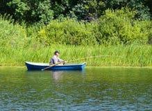 Fishing men on the boat. The lake. Fishing men on the boat Stock Photo