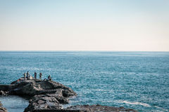 Fishing men on rocks by the japanese ocean Royalty Free Stock Photo
