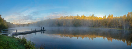 Fishing by a misty lake Stock Image
