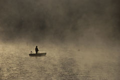 Fishing in the morning mist. A fisherman on a boat, angling in the morning mist Stock Images