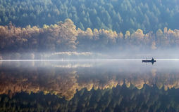 Fishing in the morning mist. One angler fishing on a misty lake Stock Image