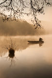 Fishing in the morning mist. One angler fishing on a misty lake Stock Photography