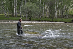 Fishing on the mountain river fishing rod. Fisherman fishing in the mountains. Trout fishing. Royalty Free Stock Image