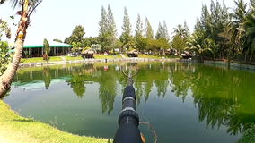 Fishing near the pond. Fishing-rod set up at the edge of a pond stock footage