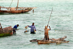 Fishing near shore, young African men fishermen go sea fishing. Royalty Free Stock Photography