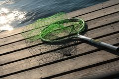 Fishing net. On wooden dock by the water. Waves sparkling in the sun stock photos