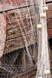Fishing net. Wet fishing net with corks is hanging on the old rusty fishing boat stock photography