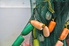 Fishing net. With buoys hanging from boat stock images