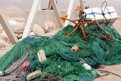 Fishing net and anchor. Fishing net with floats and rusty anchor on the dock Royalty Free Stock Photo
