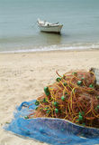 Fishing net on the beach. With small fishing boat in the background. The boat slightly out of focus Stock Photo