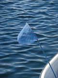 Fishing net and blue sea ripples. Fishing hand net in a boat with blue sea ripples in the background, with copy space Royalty Free Stock Photo