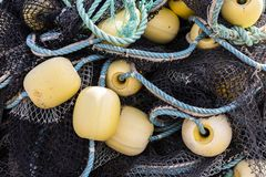 Fishing Net in Harbor Denmark. Black fishing net on the shore on a pile with yellow buoys in a harbor in Denmark stock images
