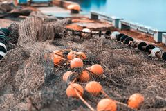 Fishing net with round floats. Fishing net green with round floats orange. The network is old and lying on the ground stock images