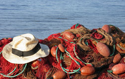 Fishing net and hat. Colourful fishing net with panama hat in front of blue sea stock image