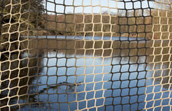 Fishing net. A lake in a forest, in the foreground a fishing net stock image