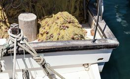Fishing net lay in wooden boat. Fishing net lay in old wooden boat Royalty Free Stock Images
