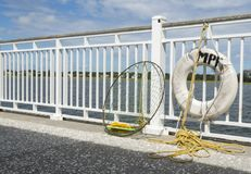 Fishing Net and Life Preserver Hung on Pier with Yellow Rope. A fishing net and life preserver hanging from railing of a pier in South Carolina Royalty Free Stock Photos