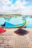 Fishing net and Luzzu colored boats at Marsaxlokk Harbor Malta. Fishing net and Luzzu colored boats at Marsaxlokk Harbor, Malta island Stock Photo