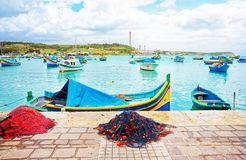 Fishing net and Luzzu colorful boats at Marsaxlokk Harbor Malta. Fishing net and Luzzu colorful boats at Marsaxlokk Harbor, Malta island Royalty Free Stock Images