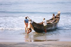 Fishing net with many fishermen on backside. Odayam beach, Varkala, India. Varkala, India - February 09, 2016: Fishing net with many fishermen on backside the Stock Images