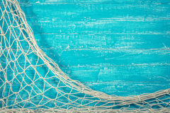 Fishing net on old blue board Royalty Free Stock Images