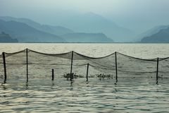 Fishing net over the lake water on the background of blurry mountains in the fog in the evening. A fishing net over the lake water on the background of blurry royalty free stock photography