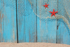 Fishing net and red starfishes against an old wooden background Royalty Free Stock Photos