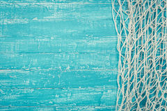 Fishing net from right side of turquoise board Royalty Free Stock Image
