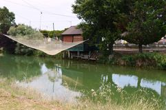 Fishing net on the river. Fishing net on the green river stock images