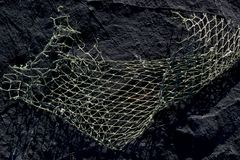Fishing net on a rock as background texture royalty free stock image