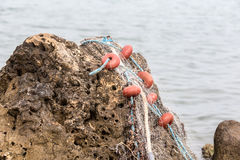 Fishing net on a rock Stock Photos