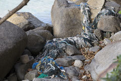 Fishing net among the rocks. Old fishing net among the rocks Royalty Free Stock Photos