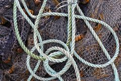 Fishing Net Rope Denmark. Black fishing net on the shore on a pile with blue rope in a harbor in Denmark royalty free stock photography