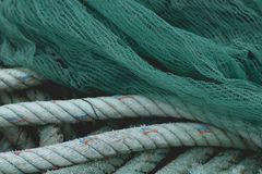 Fishing net and rope. Detail of old fishing net and rope in a harbor, abstract background or texture royalty free stock image