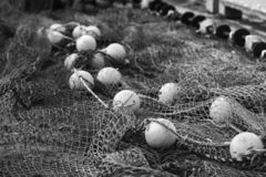 Fishing net with round floats. In black and white. The network is old and lying on the ground stock photos