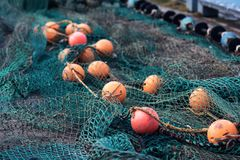 Fishing net with round floats. Fishing net green with round floats orange. The network is old and lying on the ground stock photo