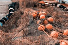Fishing net with round floats. Fishing net green with round floats orange. The network is old and lying on the ground stock photography