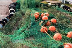 Fishing net with round floats. Fishing net green with round floats orange. The network is old and lying on the ground stock image
