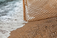 Fishing net on sandy beach at sea waves Royalty Free Stock Images