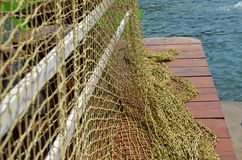 Fishing net and sea. Large fishing net on a mall with sea in background royalty free stock photo