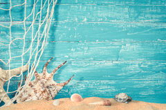 Fishing net and sea shells on sand on blue royalty free stock images