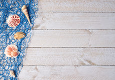 Fishing net and shells. Blue fishing net with seashells on weathered wooden boards stock photography