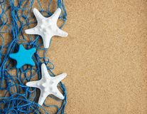 Fishing net with starfish. On a natural sand background royalty free stock image