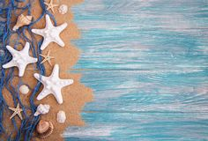 Fishing net with starfish. On a wooden background stock image