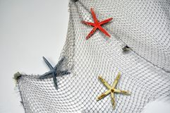 Fishing net with starfish, maritime nautical decoration over white background with copy space stock photo