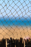 Fishing net at summer seaside on blue sky and sandy beach scenic background. Beautiful vertical maritime view Royalty Free Stock Photo