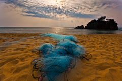 Fishing Net and Sunrise. A fishing net laying on a beach in Malaysia Stock Photo