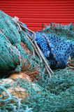 Fishing nets. A pile of colorful fishing nets in front of a red shed door Stock Photos