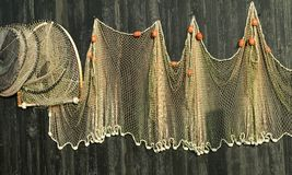 Fishing nets. Hanging on a wooden house wall royalty free stock images