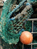 Fishing Nets. Bright orange buoy and pile of turquoise fishing nets on a dock in Polperro, a quaint fishing village in Cornwall, England Royalty Free Stock Photo